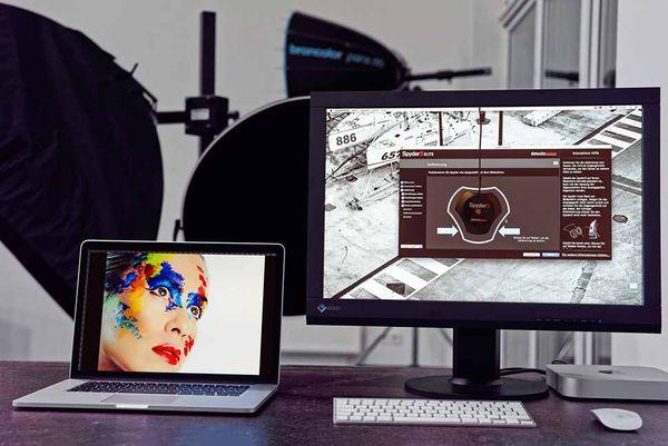 Das Spyder-Messgerät von Datacolor wird auf dem Monitor angebracht, damit es die von seiner Software erzeugten Farbfelder erfassen kann (hier am großen Monitor rechts).